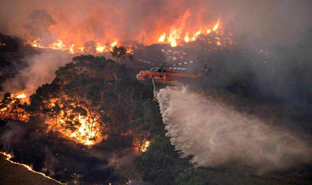 A handout photo taken and received on Dec. 31, 2019, from the State Government of Victoria shows a helicopter fighting a bushfire near Bairnsdale in Victoria's East Gippsland region. (AFP Photo/ State Government of Victoria)